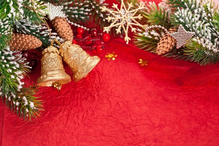 Christmas border from branch and decorations on red background photo