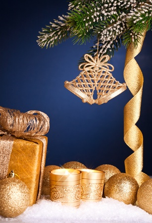 Christmas tree decorations in snow on dark blue background. Shallow depth of field photo