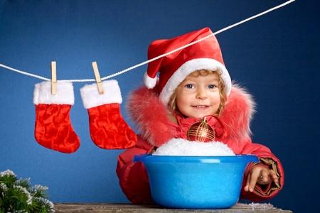 wash basin: Child in Santa hat washing in basin. Christmas concept