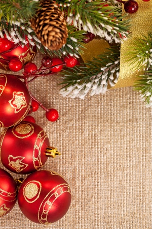 Christmas frame with branch and decorations on burlap background photo