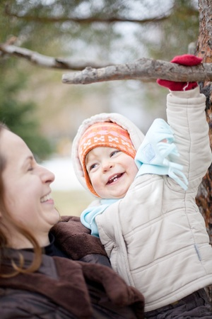 Happy woman holding baby on hand in winter park photo