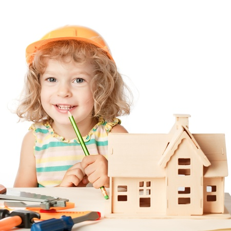 builds: Happy child builds house. Isolated on white