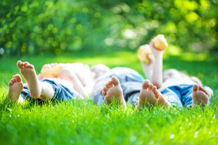 family park: Children laying on grass. Family picnic in spring park Stock Photo