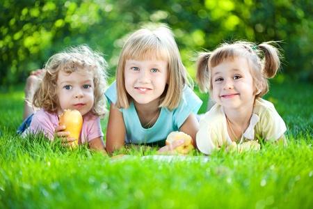 ni�os leyendo: Los ni�os la lectura del libro de familia de picnic en el parque de la primavera