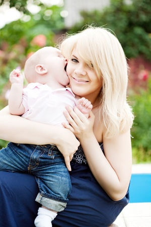 Baby boy kissing mother in summer park Stock Photo - 11485739