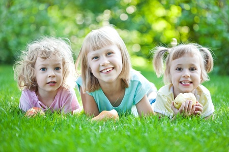 Happy children laying on grass. Family picnic in spring park photo