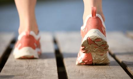 foot bridge: Feet of female running to water Stock Photo