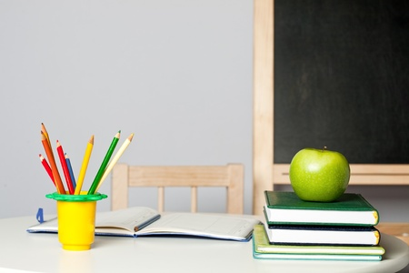 Desk with apple, pencil, notebook and textbook in class. School concept photo