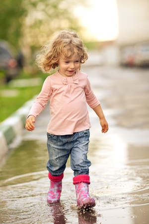 Cute child walking on puddle in autumn photo