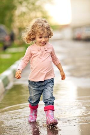 botas de lluvia: Niño lindo caminar por charcos en otoño Foto de archivo