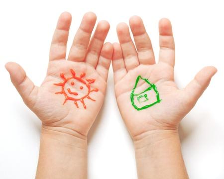 case colorate: Disegnato il sole e casa sulle mani bambino. Primavera concetto