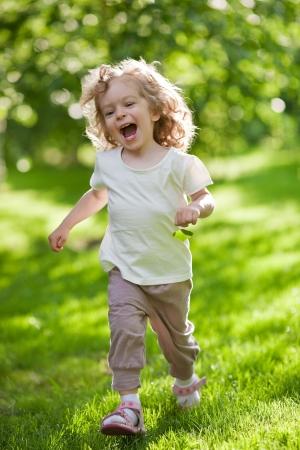 enfant qui court: Belle enfant va dans des sports de l'�t�. La nature de fond vert Banque d'images
