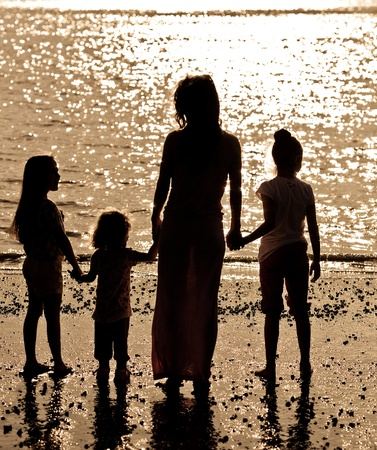 Silhouette of woman with children on sea beach Stock Photo - 11745954
