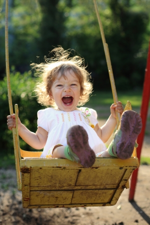 toddler playing: Laughing child on swing in summer park  Stock Photo