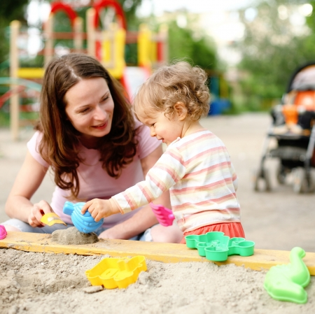 sandbox: Happy family on playground in summer Stock Photo