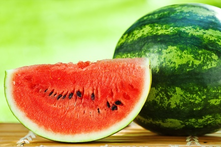 Juicy slice of big watermelon against natural green background in spring photo