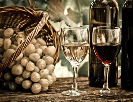 vintage look: Bottiglie di vino, due bicchieri e grappolo d'uva nel paniere contro il vigneto in primavera. Look vintage Archivio Fotografico