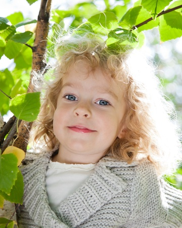 Beautiful child in green spring leaves against sunny natural background Stock Photo - 11870379