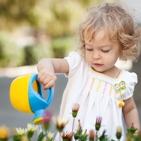 Beautiful child watering spring flowers against green natural background photo