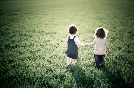 Two children going in spring green field photo