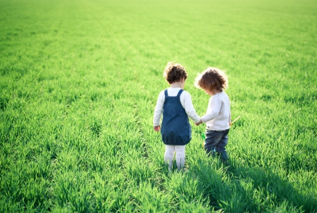 Two children going in spring green field Stock Photo