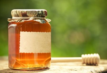 Honingpot met blanco papier label en houten stok op tafel tegen groene lente natuurlijke achtergrond