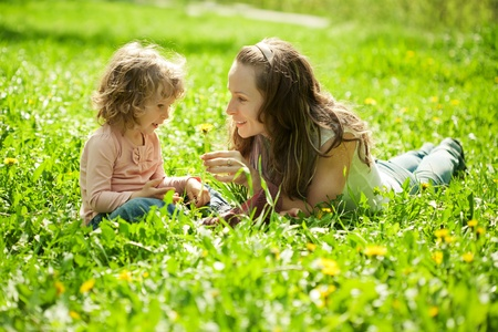 Happy family playing on green frass in spring park Stock Photo - 11936372