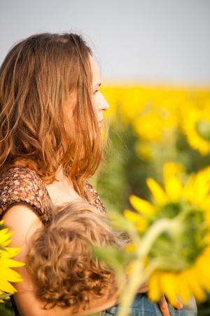 borstvoeding: Jonge vrouw haar baby borstvoeding in het voorjaar zonnebloem veld
