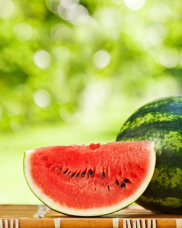 Big slice of juicy watermelon against natural green background in spring photo
