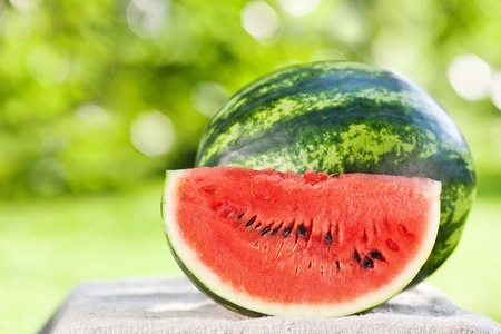 Fresh juicy watermelon against natural green background in spring park Stock Photo