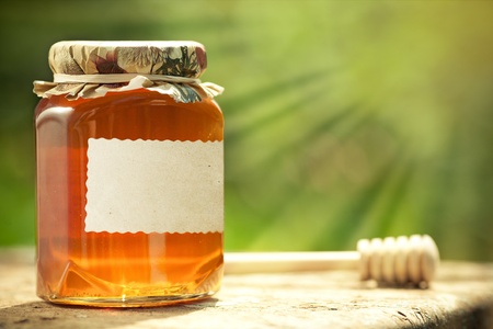 honey jar: Honey jar with blank paper label and wooden stick on table against green spring natural background