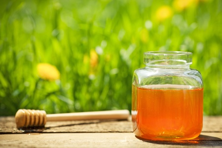Flowery honey in glass jar on wooden table against spring natural green background photo