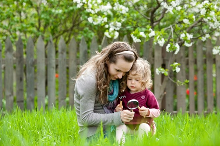 Happy family playing outdoors in spring garden against flowery background photo
