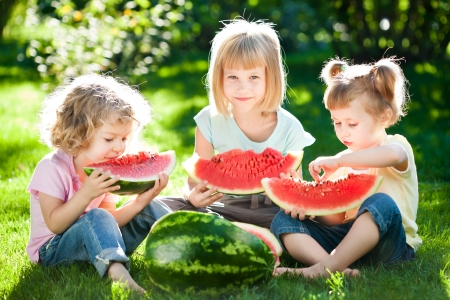 Group of happy children eating watermelon outdoors in spring park photo