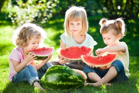 Groupe d'enfants heureux manger la pastèque en plein air dans le parc du printemps Banque d'images