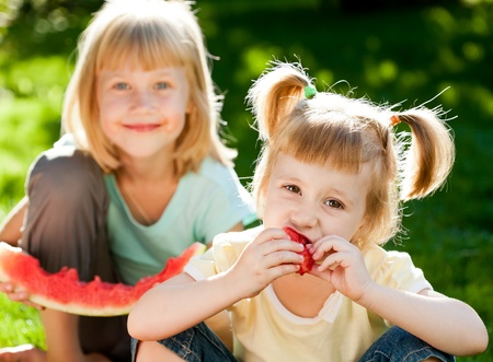 Happy children eating watermelon outdoors in spring park