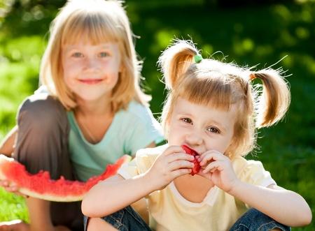 Los niños felices comiendo sandía al aire libre, en la primavera de parque Foto de archivo