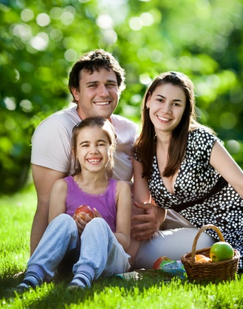 Happy family having fun outdoors in spring park against natural green background photo