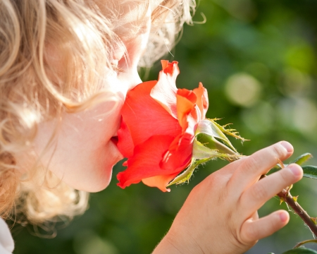 Beautiful child with flower against spring green background. Ecology concept photo