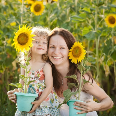 Beautiful woman and child with sunflower in spring field photo