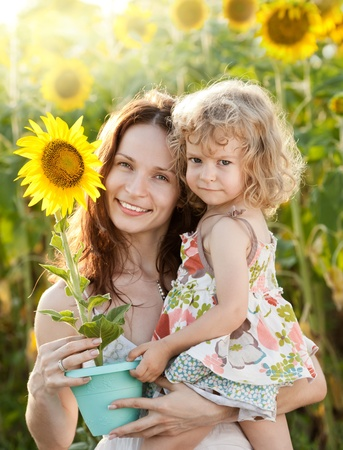 yellow earth: Beautiful woman and child with sunflower in spring field Stock Photo