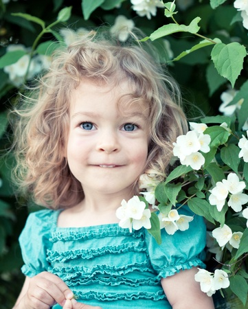 Happy child with jasmine flowers outdoors in spring park photo