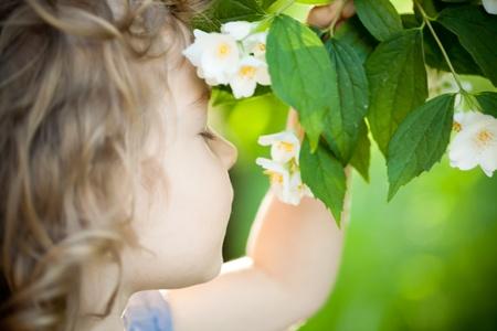 Hermoso niño con la flor de jazmín contra el muelle de fondo verde. Ecología concepto