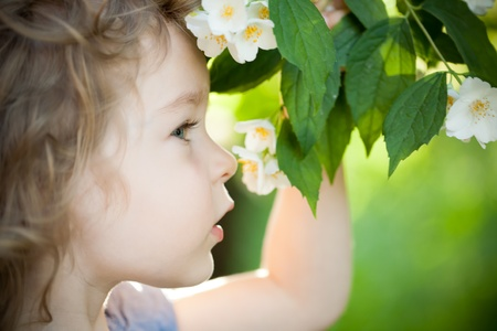 Beautiful child with jasmin flower against spring green background. Ecology concept photo
