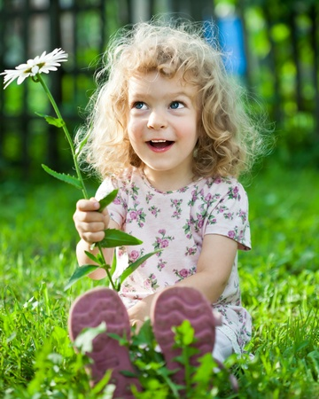 Happy smiling child playing outdoors in spring garden photo