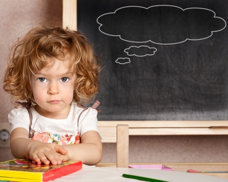 Funny smiling child in a class against blackboard with speech bubbles. School concept photo