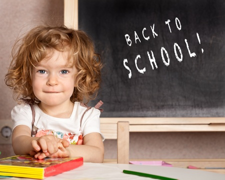 Happy smiling child in a class against blackboard with text Back to school! photo