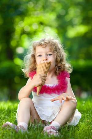 Beautiful child eating ice-cream outdoors in spring park against natural green background photo