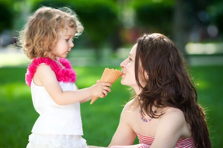 Woman and child eating ice-cream in spring park photo
