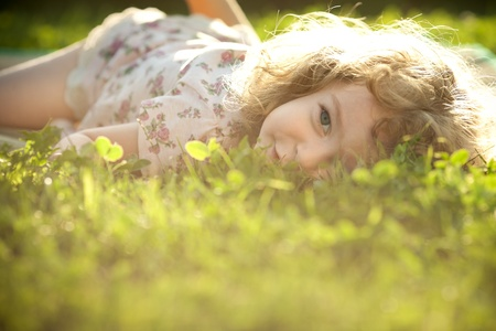 Beautiful child lying on a grass on a spring meadow in sunshine